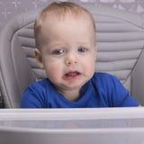 Umgekipptes Kleinkind in einem Babystuhl, der Kamera betrachtet stockfoto