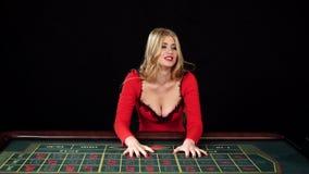 Umgekipptes Mädchen, das nahe dem Spieltisch, Schwarzes, Zeitlupe sitzt