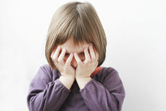 Umgekipptes Mädchen mit ihren Händen auf ihrem Gesicht Stockbild