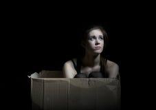 Umgekipptes Mädchen, welches das Sitzen in der Pappschachtel aufwirft Stockfoto