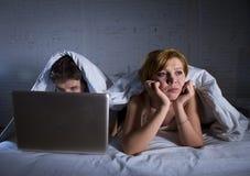 umgekipptes unzufriedenes der jungen Frau und frustriert im Bett während Ehemannarbeit über den Computerlaptop, der sie ignoriert lizenzfreies stockfoto