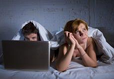 umgekipptes unzufriedenes der jungen Frau und frustriert im Bett während Ehemannarbeit über den Computerlaptop, der sie ignoriert stockfoto