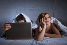 umgekipptes unzufriedenes der jungen Frau und frustriert im Bett während Ehemannarbeit über den Computerlaptop, der sie ignoriert lizenzfreie stockfotografie