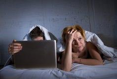 umgekipptes unzufriedenes der jungen Frau und frustriert im Bett während Ehemannarbeit über den Computerlaptop, der sie ignoriert lizenzfreies stockbild