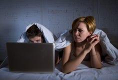 umgekipptes unzufriedenes der jungen Frau und frustriert im Bett während Ehemannarbeit über den Computerlaptop, der sie ignoriert stockfotografie