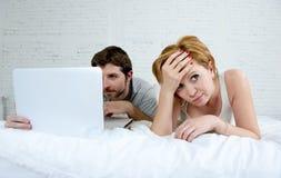 Umgekipptes unzufriedenes des attraktiven Frauengefühls und frustriert im Bett mit seinem Ehemann während die Mannarbeit über den lizenzfreie stockfotografie