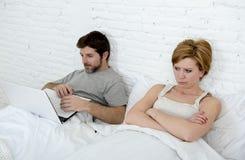 Umgekipptes unzufriedenes des attraktiven Frauengefühls und frustriert im Bett mit seinem Ehemann während die Mannarbeit über den stockfotografie