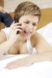 Umgekipptes weibliches blondes mit einem Mobiltelefon Stockbilder
