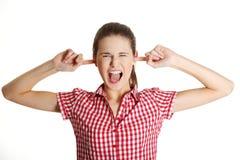 Umgekipptes weibliches jugendlich, ihre Ohren verstopfend. Stockbild