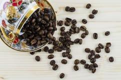 Umgeworfene PorzellanKaffeetasse mit Kaffeebohnen auf Holztisch Lizenzfreie Stockfotos