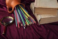 Umgeworfener Krug mit farbigen Bleistiften, Lupe und alten Büchern auf dem Schreibtisch Stilisierte Ansicht von Retro- Gegenständ Stockfoto