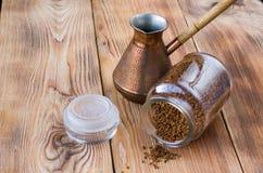 Umgeworfenes cezve mit Kaffeebohnen, Sch?ssel mit gemahlenem Kaffee auf Holztisch lizenzfreies stockfoto
