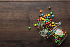 Umgeworfenes Glasgefäß voll bunte Bonbons stockbilder
