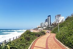 Coastal City Landscape in Umhlanga Durban South Africa. UMHLANGA, DURBAN, SOUTH AFRICA - OCTOBER 31, 2017: Many unknown visitors and promenade on beachfront Stock Images