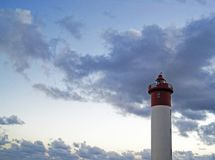 UMHLANGA ROCKS LIGHTHOUSE AGAINST CLOUDS WITH FAINT SUNSET HUES. View of soft hues on clouds in the sky with Umhlanga Rocks lighthouse royalty free stock photo