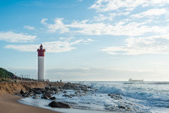 Umhlanga Rocks Lighthouse with fishermen and people walking on the promenade. Ship on the Indian Ocean in the background Stock Photography