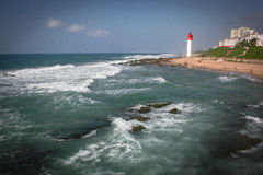 Umhlanga Waves. Incoming tide on Unhlanga beach with lighthouse stock images