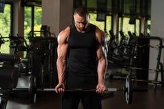 Umięśnionej samiec Wzorcowi Ćwiczy bicepsy Z Barbell Zdjęcie Stock