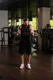 Umięśnionej samiec Wzorcowi Ćwiczy bicepsy Z Barbell Zdjęcia Stock