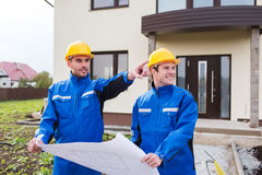 Uśmiechnięci budowniczowie wskazuje palec z projektem Zdjęcia Royalty Free