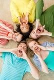 Uśmiechnięci ludzie łgarskiego puszka na podłogowym i krzyczącym Fotografia Royalty Free