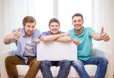 Uśmiechnięci męscy przyjaciele trzyma białą puste miejsce deskę Fotografia Stock