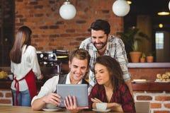 Uśmiechnięci przyjaciele patrzeje cyfrową pastylkę Fotografia Royalty Free