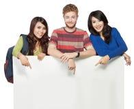 Uśmiechnięci ucznie trzyma pustego białego sztandar odizolowywający na białych półdupkach Obraz Stock