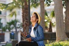 Uśmiechnięta amerykanin afrykańskiego pochodzenia kobieta słucha muzyka na telefonie komórkowym Obrazy Royalty Free