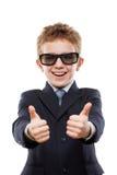 Uśmiechnięta dziecko chłopiec jest ubranym okularów przeciwsłonecznych gestykulować w garniturze Zdjęcie Royalty Free