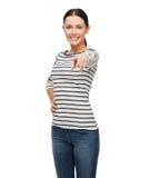 Uśmiechnięta dziewczyna wskazuje przy tobą w przypadkowym clother Zdjęcie Royalty Free