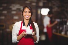 Uśmiechnięta kelnerka trzyma filiżankę kawy Obrazy Royalty Free
