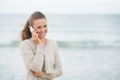 Uśmiechnięta kobieta opowiada telefon komórkowego na zimno plaży Fotografia Stock