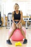 Uśmiechnięta kobieta robi sprawności fizycznej ćwiczy z dysponowaną piłką Zdjęcia Royalty Free