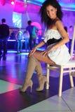 Uśmiechnięta kobieta w sukni siedzi na krześle w noc klubie Zdjęcie Royalty Free