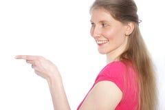 Uśmiechnięta kobieta wskazuje z jej palcem Zdjęcie Royalty Free