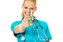 Uśmiechnięta kobiety lekarka, pielęgniarka z stetoskopu mienia strzykawką lub Zdjęcia Stock