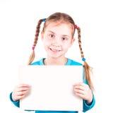 Uśmiechnięta mała dziewczynka trzyma biel kartę dla ciebie próbka tekst Obrazy Stock