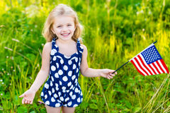 Uśmiechnięta mała dziewczynka z długą blondynu mienia flaga amerykańską Zdjęcie Royalty Free