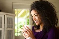 Uśmiechnięta młoda kobieta siedzi w domu cieszący się filiżankę kawy Obrazy Royalty Free