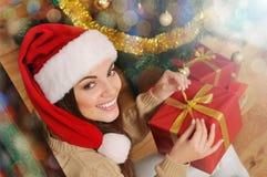 Uśmiechnięta młoda kobieta z teraźniejszości pudełkiem w Santa kapeluszu na bożych narodzeniach t Zdjęcia Royalty Free