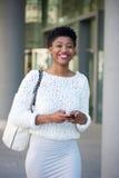 Uśmiechnięta młodej kobiety dosłania wiadomość tekstowa int on miasto Obrazy Royalty Free