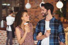 Uśmiechnięta modniś para z oddalonymi filiżankami Obrazy Royalty Free