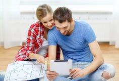 Uśmiechnięta para patrzeje pastylka komputer osobistego w domu Fotografia Stock