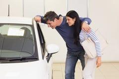 Uśmiechnięta para patrzeje wśrodku samochodu Zdjęcie Stock