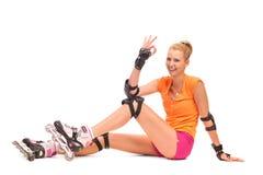 Uśmiechnięta rolkowego łyżwiarstwa dziewczyna pokazuje OK znaka. Zdjęcie Royalty Free