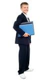 Uśmiechnięte dzieciaka mienia kartoteki, młoda biznesowa chłopiec Fotografia Stock
