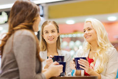 Uśmiechnięte młode kobiety z filiżankami w centrum handlowym lub kawiarni Obraz Stock