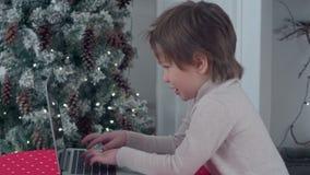 Uśmiechniętej chłopiec pisać na maszynie list Święty Mikołaj na laptopie blisko choinki zbiory