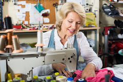 Uśmiechniętej dojrzałej kobiety krawiecka używa szwalna maszyna Obrazy Royalty Free